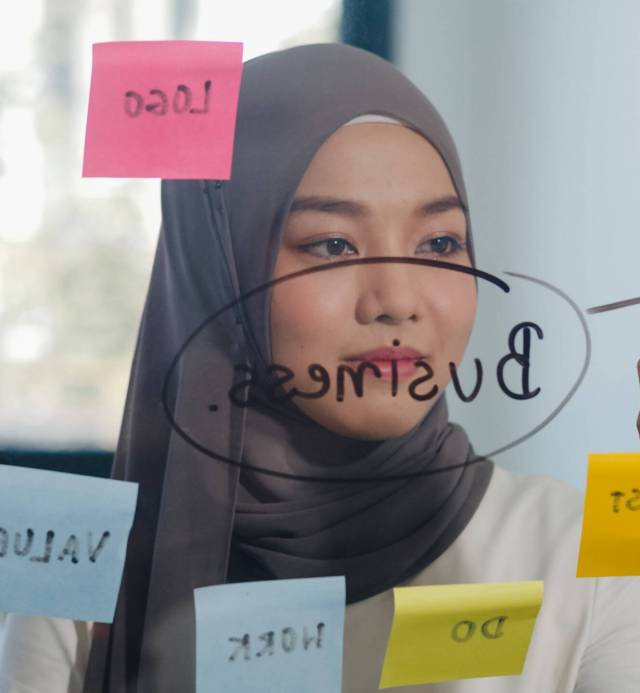 Asia muslim lady write information, strategy, reminder on glass board in new normal office. Working from home, remotely work, self isolation, social distancing, quarantine for coronavirus prevention.