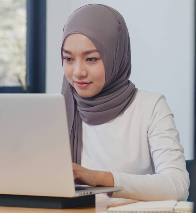 Beautiful Asia muslim lady casual wear working using laptop in modern new normal office. Working from home, remotely work, self isolation, social distancing, quarantine for coronavirus prevention.